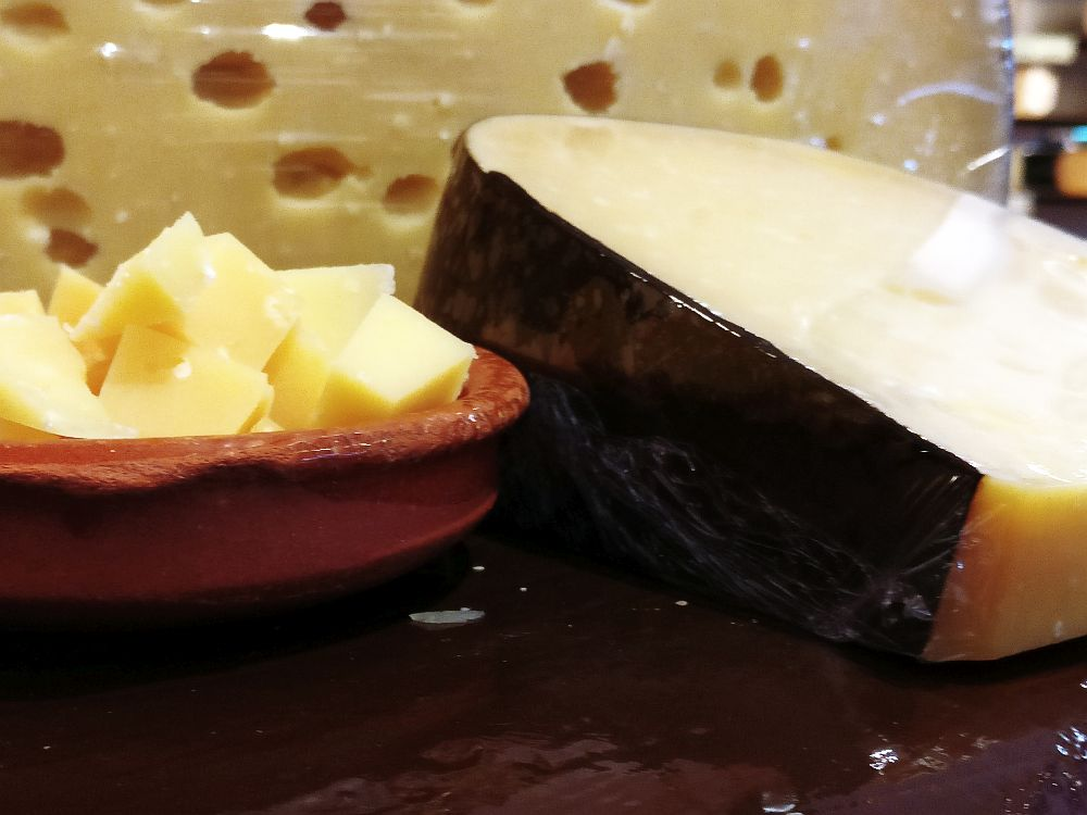 A close-up of, on the right, a wedge of cheese with a black wax out shell and, on the left, small cubes of cheese in a shallow bowl. Behind is a larger cheese with a lot of holes.