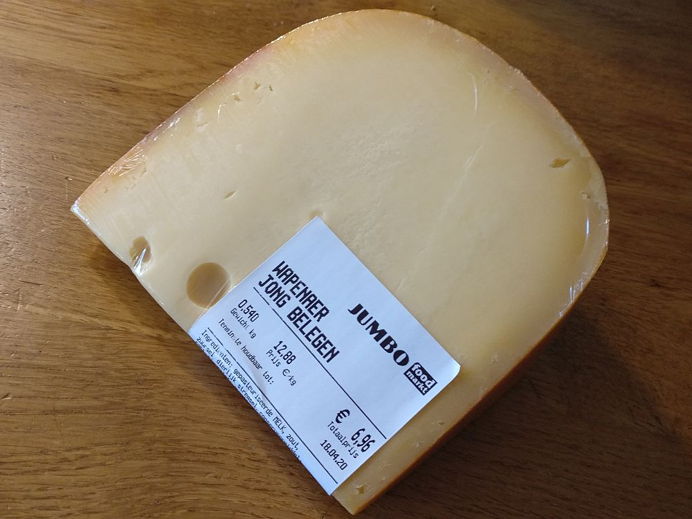 A wedge of cheese wrapped in plastic with a supermarket label, translated: Jumbo food market, Wapenaer Jong Belegen, weight 0.540 kg, price in euro/kg 12.88, total price 6.96.