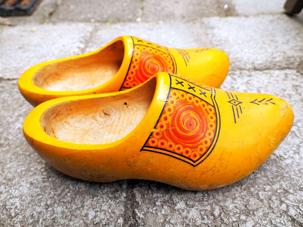 A pair of typical Dutch clogs, painted for the tourist market. They are made of wood but painted on the outside in yellow, with a decorative pattern on the front from the top edge to the toe: red circles on each side, xxx down the middle in black, and a few simple lines on the toe.