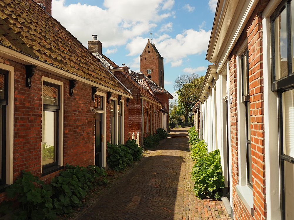 Looking almost straight down the road, small houses with tall windows along both sides of a narrow brick-paved street. At the end of the street a square brick church tower peeks up above the last house.