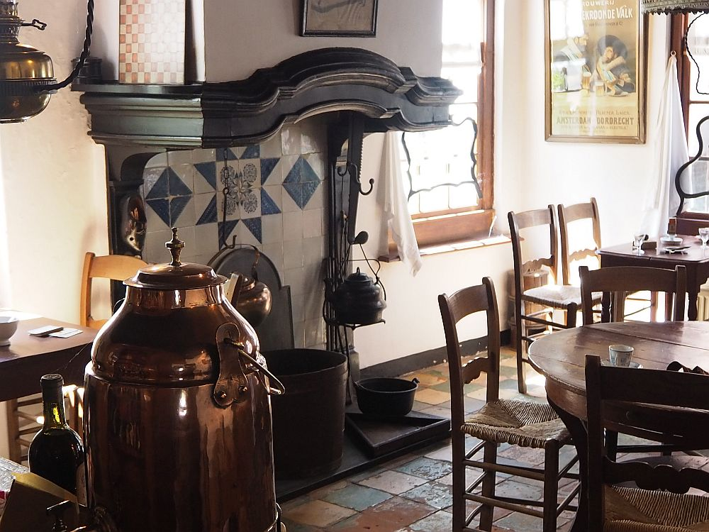 A chimney with blue and white tiles at its back wall (presumably Delft), a large kettle hangs in its center and another to the side. The mantel is dark would and shaped in a curve at the center, but otherwise relatively plain. In front of the fireplace is a round table, partially visible, with simple chairs around it and a teacup and saucer in front of one of the places. Beyond that, a window and a square table with chairs. IN the foreground, a big copper container of some sort: for coffee, perhaps.