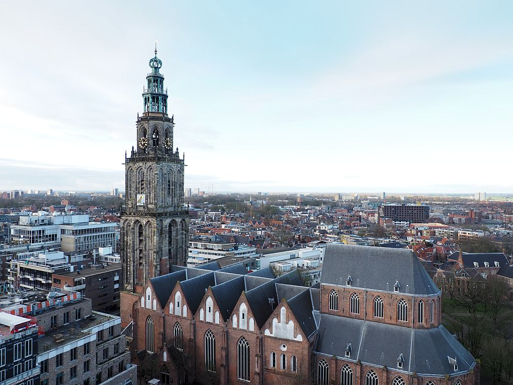 Looking slightly down at the Martinikerk (St. Martin's church) with the Martinitoren at its front. The church has gothic arches but no buttresses. The tower is red brick at the bottom (matching the church) and grey stone above. It has gothic arches too, in several levels, like a very tall, narrow wedding cake. At the top is a green (copper, I assume) tower top, with a round bulb shape at the top.