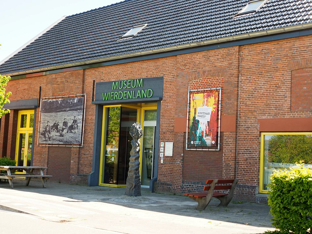 The front of the museum: a plain, one story red-brick building with doors in the center and a few signs advertising special exhibitions.