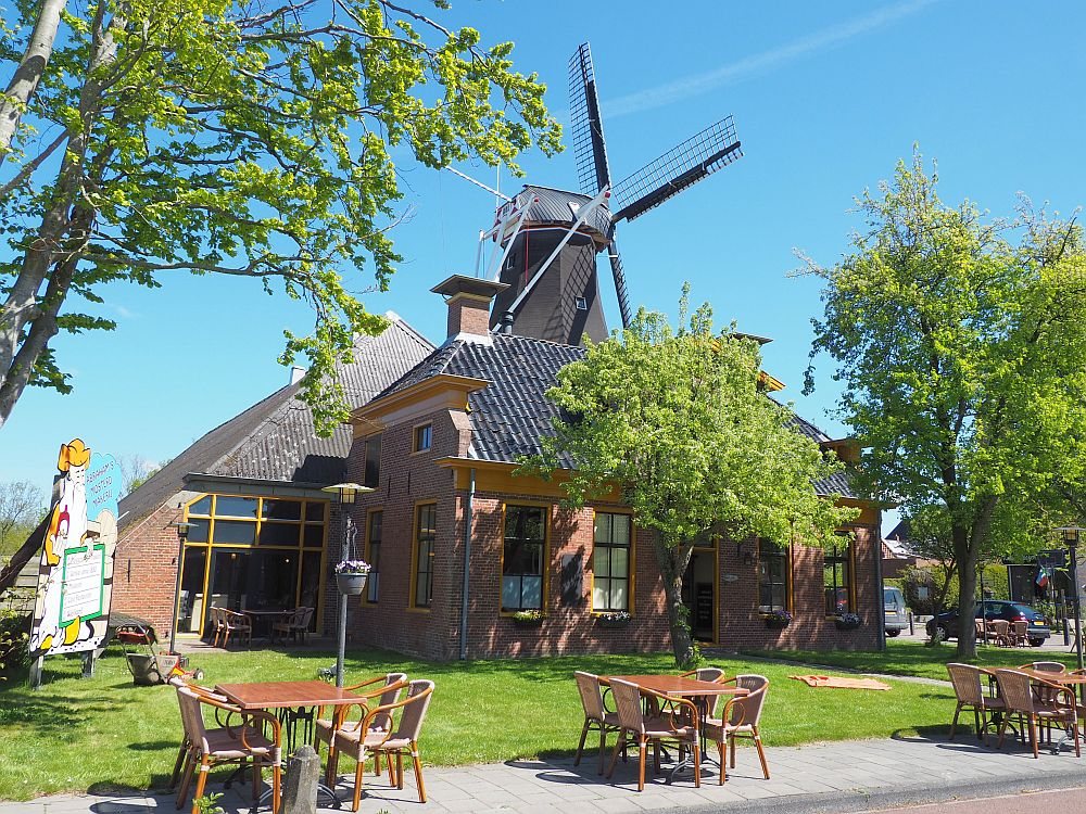 The mustard factory looks like a typical Groningen farmhouse: red brick with a much bigger barn behind and attached to it. Behind that a windmill (De Lelie) Is partially visible: just the top and the vanes.