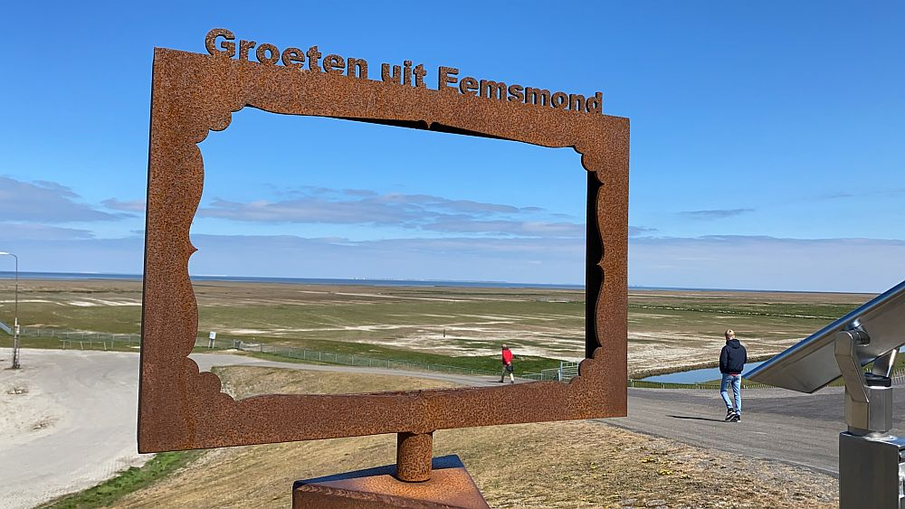 """A large rectangular rusty steel frame with the words """"Groeten uit Eemsmond"""" frames a very flat scene of grass and sand into the distance, where a line of blue sea is visible, with a barely perceptible rise of land beyond it. A few people walk toward the sea along a dirt path next to the frame."""