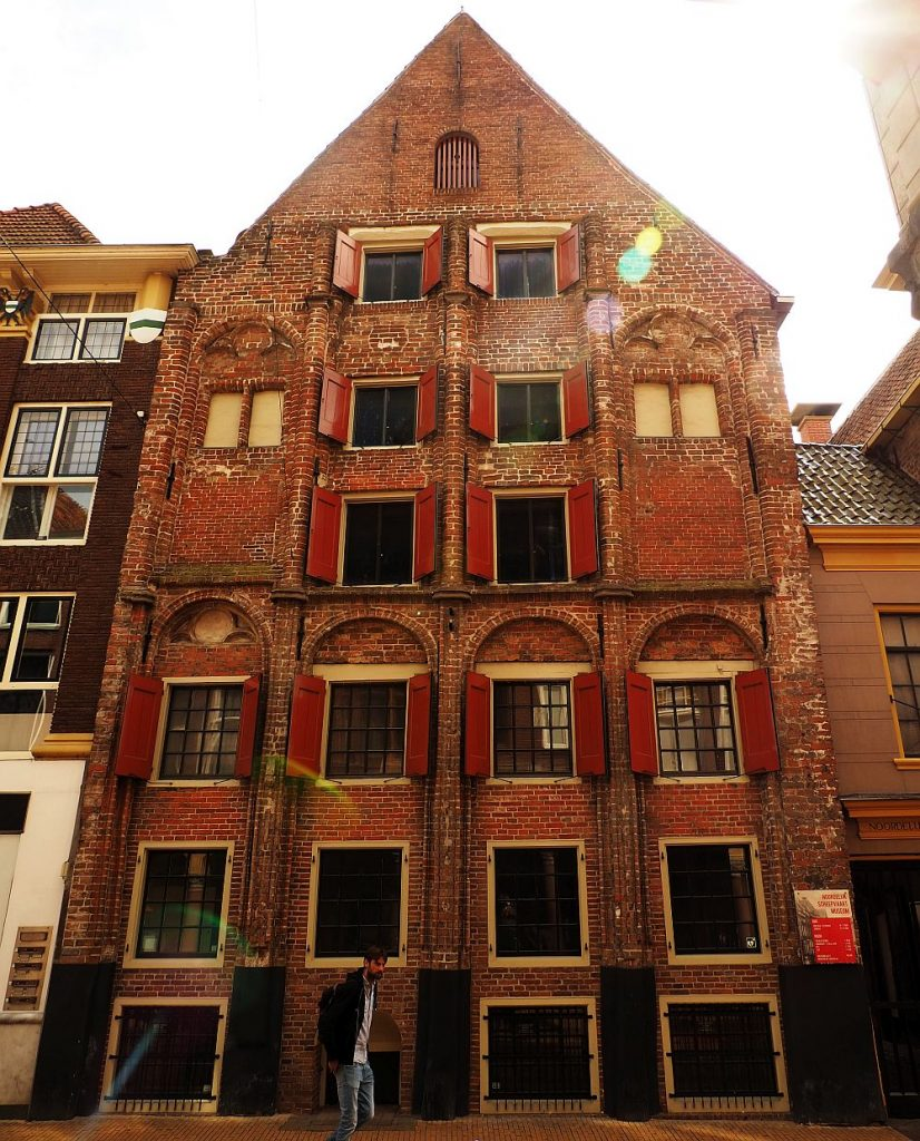 A very old brick building in a row. It appears to be six or seven stories high. Some of the upper windows have red shutters. Most of the floors have 4 windows across.