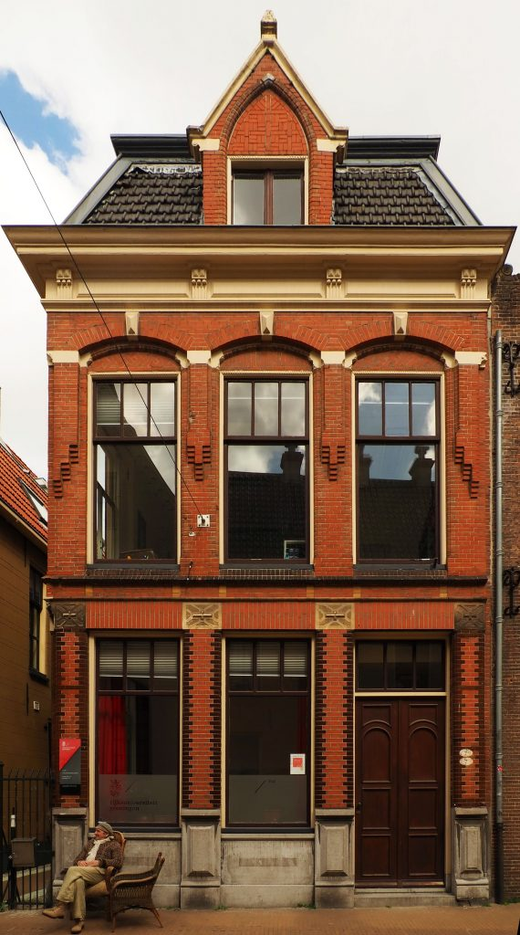 A two story row house. The grown floor has two tall windows and a door. The upper floor has three tall windows across. Above that, at the attic level, is one single dormer window. The building is red brick, with a wooden door. There are brick decorations between the upper windows and dark bricks along the edges of the lower windows.