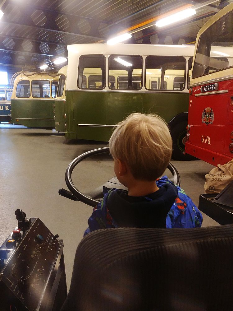 In the background, a row of buses, only the back ends visible in this photo. In the foreground, a blond child with his back to the camera. He is sitting in a driver's chair and pretending to steer a very large steering wheel.