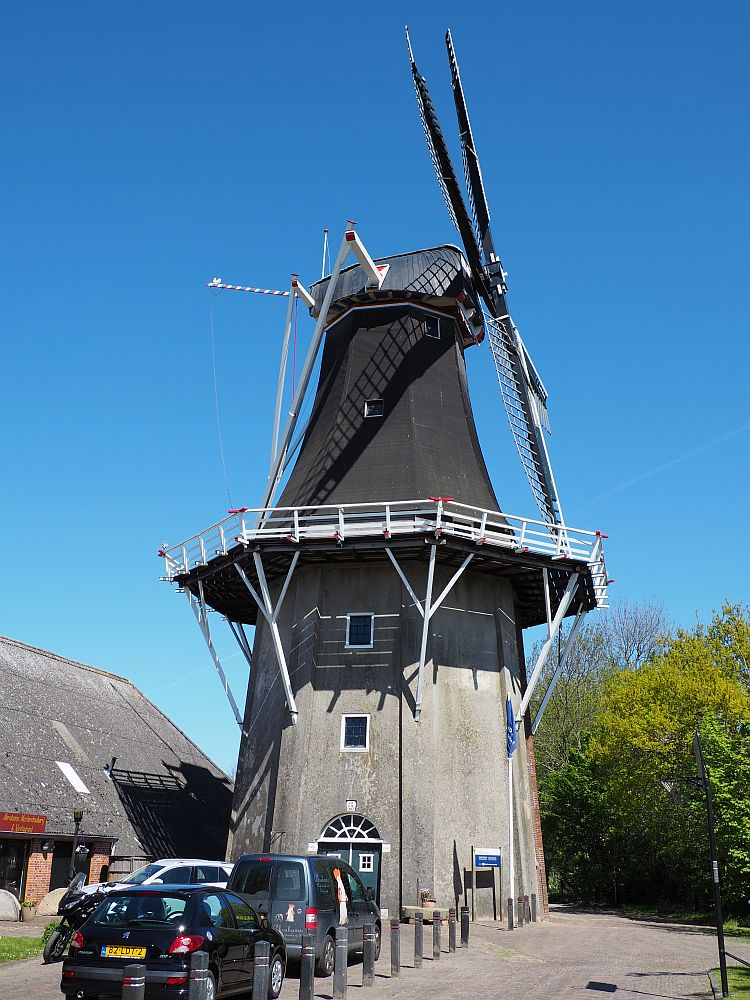 """The windmill is quite tall: A door is visible at the base, with two small windows above it indicating two additional stories above it. Above that is the """"balcony"""" all around the mill, which appears to be six or eight-sided. Above that, it's about the same height as below the balcony, making the total height about 6 stories. This is a side view, so the vanes are on the right."""