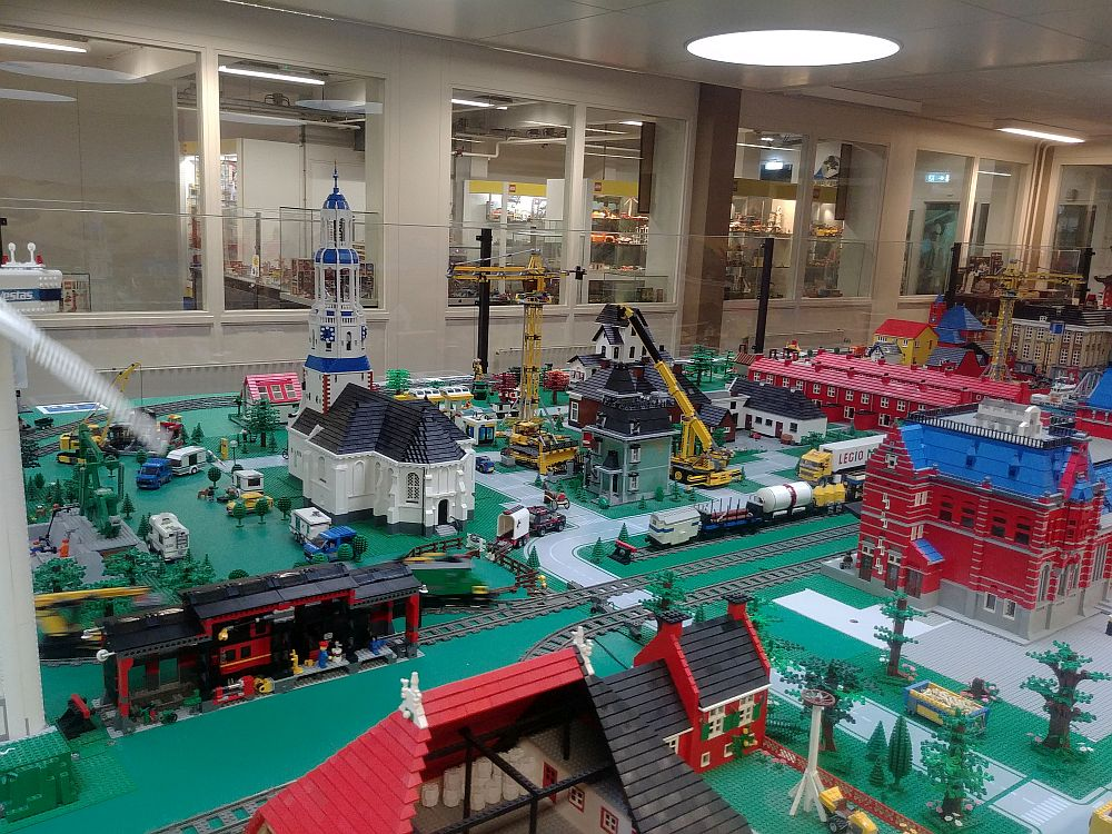A large table covered with Lego constructions: a church, various other buildings, cars, trucks, trains, etc. Through windows in the back, more Lego can be glimpsed.