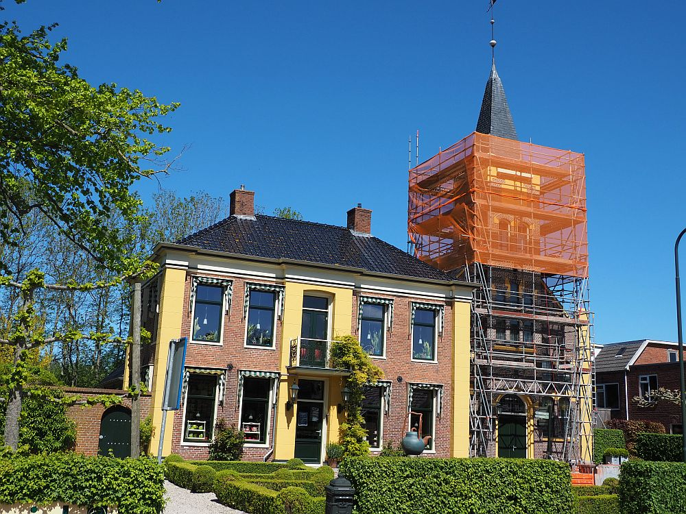 A stately-looking house, red brick and yellow plaster: symmetrical, with two stories, two doors in the center, a small balcony between them, and two windows on either side on both stories. Next to  the house is a church with a steeple, but it isn't very visible because it is covered in scaffolding.
