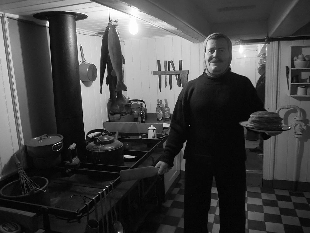 A manniken of a man stands, wearing black pants, a dark sweater, and a balaklava (but showing his face. He smiles at the camera. In his left hand is a plate with a pile of pancakes and in the right he holds a spatula. He stands next to a large cast-iron stove, which holds a large frying pan, a big pot, and a kettle. Other kitchen supplies are visible behind him, as well as several fish hanging from the ceiling.