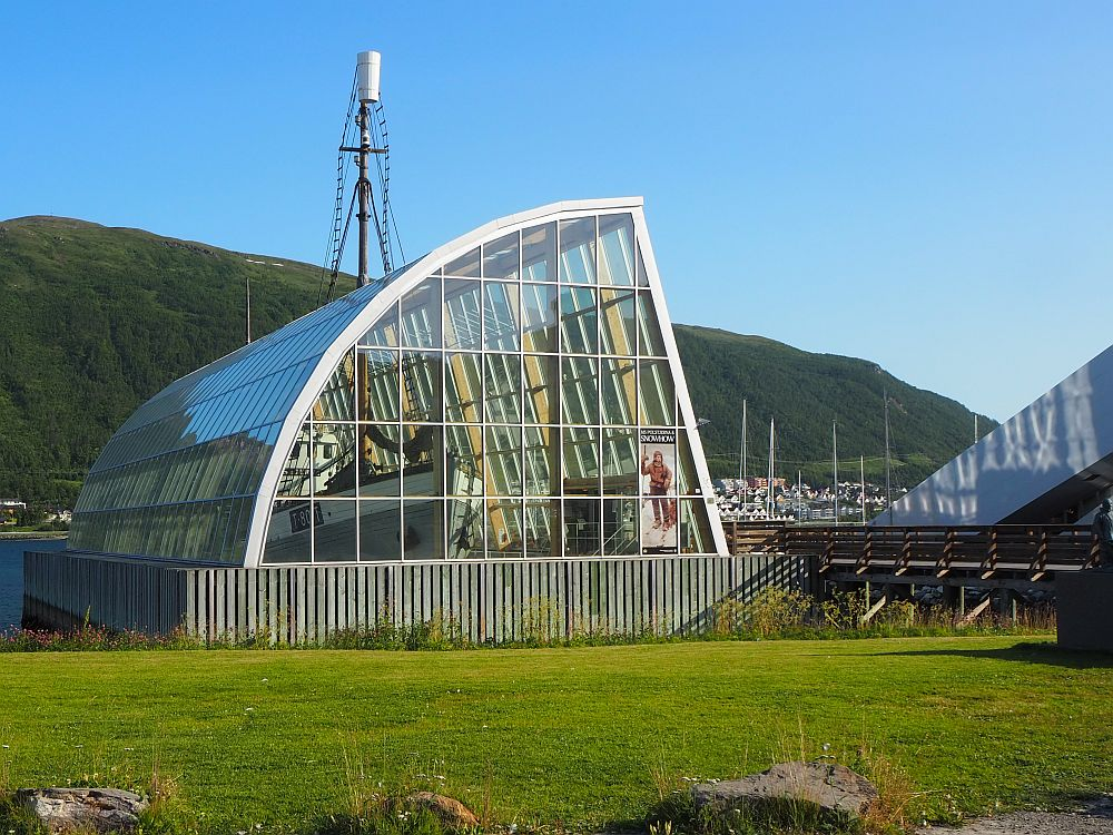 The glass building is basically shaped like a quarter of a cylinder, placed on on the flat sides. the side facing right is also flat and the side facing left is curved. The boat can be seen through the glass.