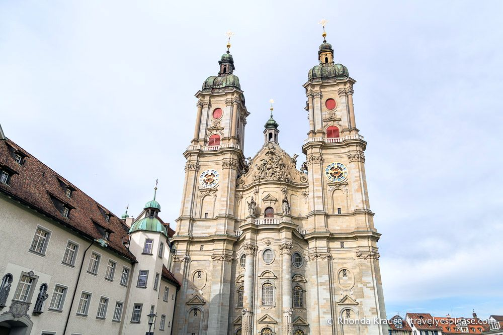 The front view of the Abbey of St Gall, white stone, ornate gables and with two spires. One of the UNESCO sites in Switzerland