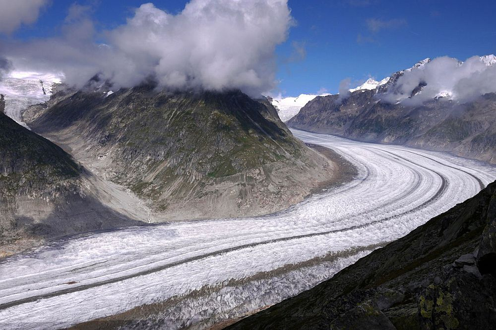 The glacier looks almost like a snow-covered road, winding from bottom left to middle right and back to the left behind a mountain. The photo looks down on the glacier, with mountains on the opposite side.