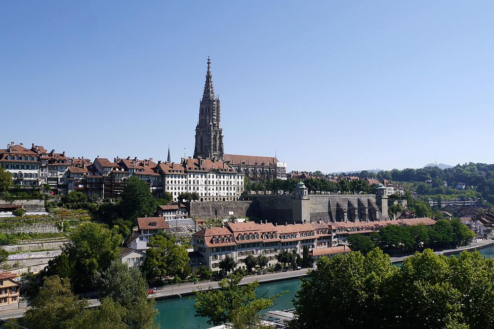 In the foreground, the bend of a river. On the other riverbank, a clustered town on the side of a hill. At the top, a church with a very tall tower. Berne is one of the UNESCO sites in Switzerland.