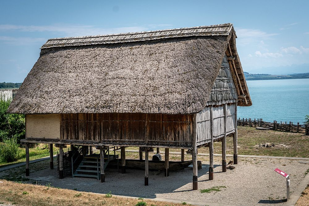 A thatch-roofed, wood-sided hut, standing on stilts.