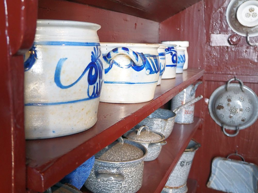 On a red-painted shelving unit, a row of simple pots: white ceramic with simple blue decorative paint. Below them, a row of enamelled metal pots, all in a gray pattern.