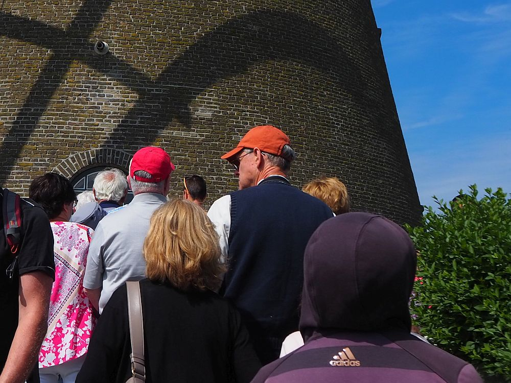The backs of a group of tourists, with the brick wall of the windmill beyond them.
