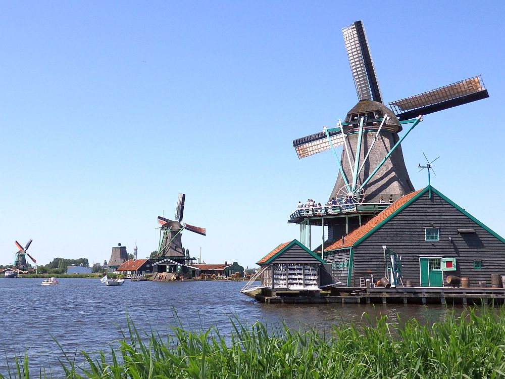 KInderdijk or Zaanse Schans? Three windmills are visible in this picture along a body of water. The nearest one seems to be six-sided and is perched on top of the roof of a house (but I think it's a workshop/factory). All are made of wood, and the house is on stilts above the water.