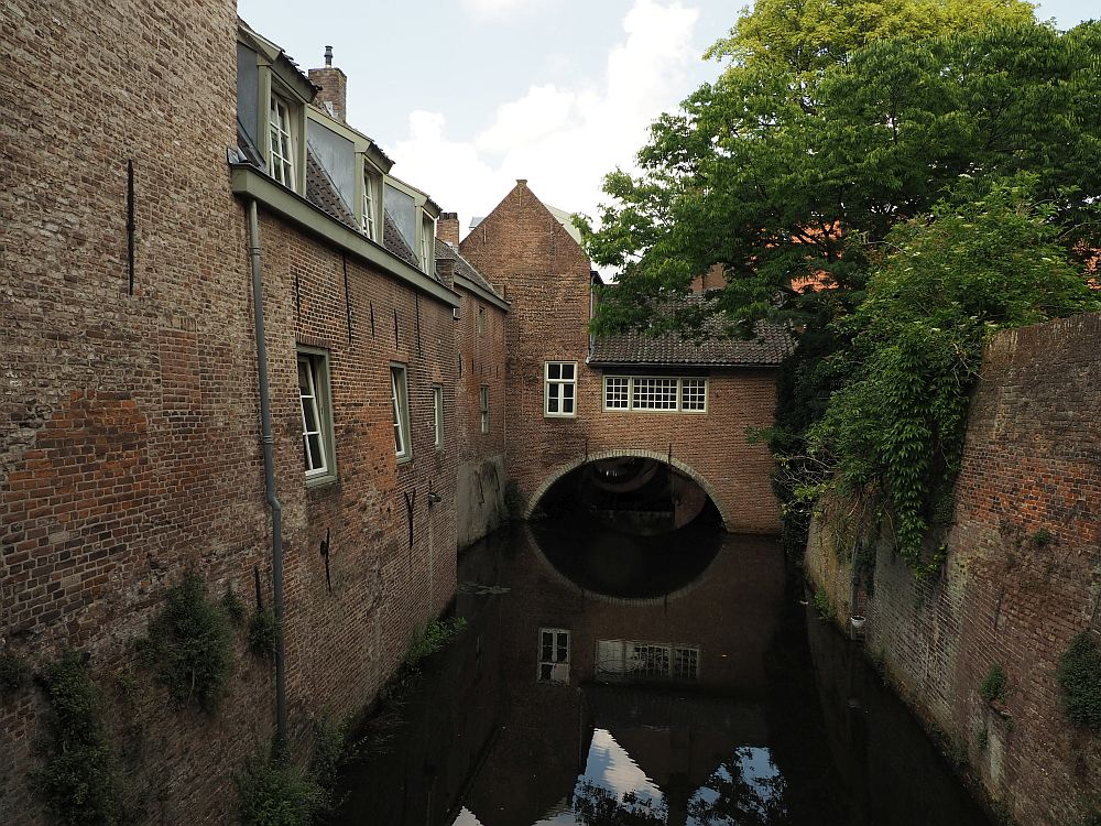 A small, straight canal down the middle of the photo disappears under and archway with a small brick building spanning the archway. A plain brick wall on the right, a tree top showing over it and dangling down its side. On the left, also a brick wall, but this one is the back side of a row of houses, with a single row of windows down the row, and gabled windows, again a single row, on the upper story.