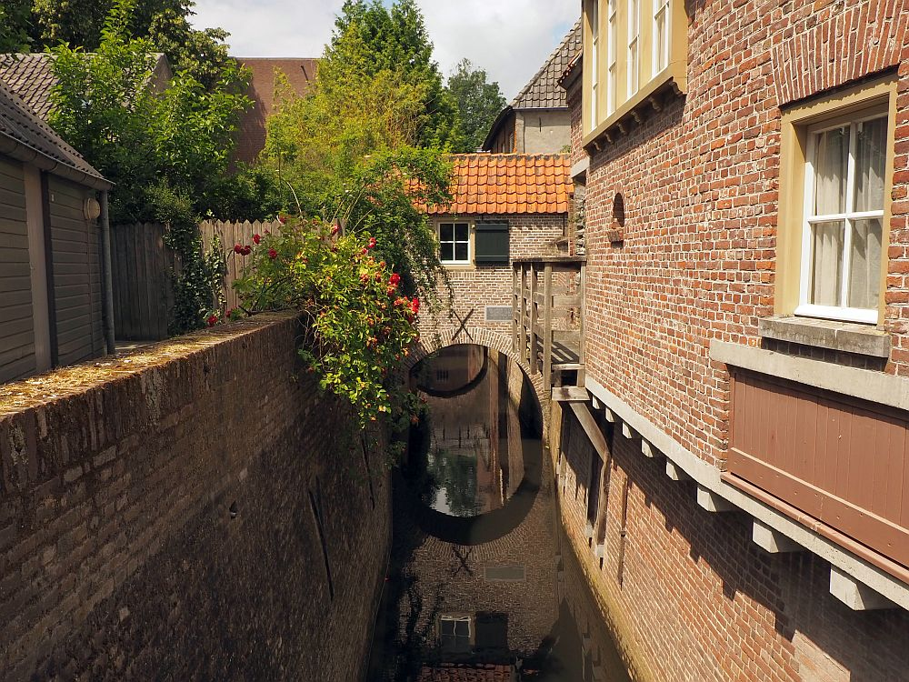 A canal-like stream down the middle going under an archway at the back of the view. Brick walls on both sides. The right side has a house above the wall, with windows on the wall. The left side has a walkway behind the wall. The archway at the back has a house on it, but only quite small from the looks of it: just one window above the stream.