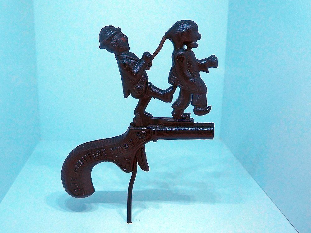 The cap pistol looks like a small black gun, but on top of the barrel are two human figures, also black metal. The one on the left is a man, presumably white, in a bowler hat. The one on the right is a Chinese man, indicated by his long braided hair. The man on the left is both pulling the braid and kicking the Chinese man in the butt at the same time. It looks like the cap would be in the Chinese man's mouth, which would snap shut when the trigger is pulled.