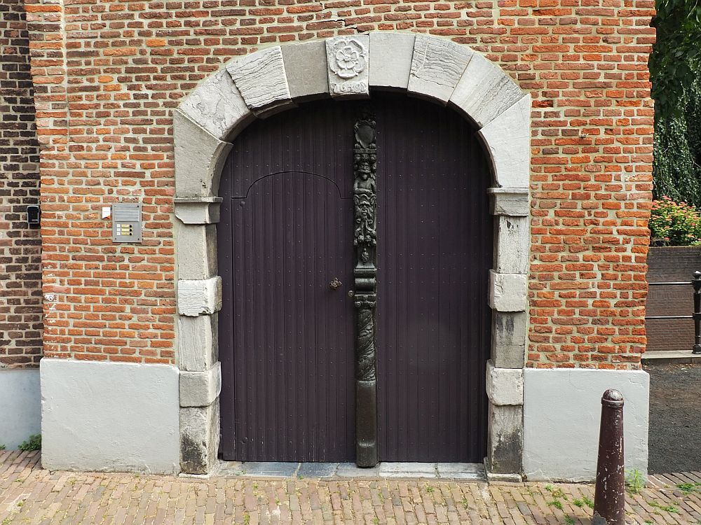 The brick building has a large archway that accommodates a double door. The door is wooden and plain, except for the vertical element down the middle, which is ornately carved. the archway is edged with stone, and the middle one above the door has a simple flower carved int oit.