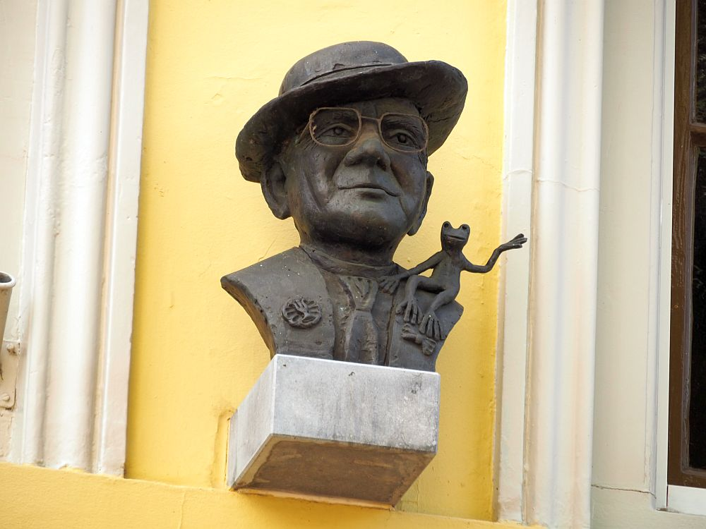 A bust of a man wearing a tie, glasses and a hat at an angle on his head. On his shoulder, a frog sits, its legs hanging down the man's shoulder and one foot/hand? waving in the air.