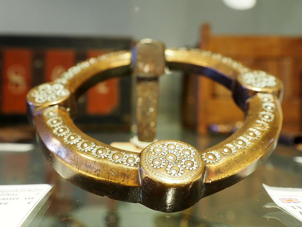 The ring looks like it might be bronze, with a pattern of embossed flowers closely imprinted around the top surface. At four points there is a round knob, also embossed with a cluster of the same tiny flower pattern. Skogar Museum, Skogar Iceland