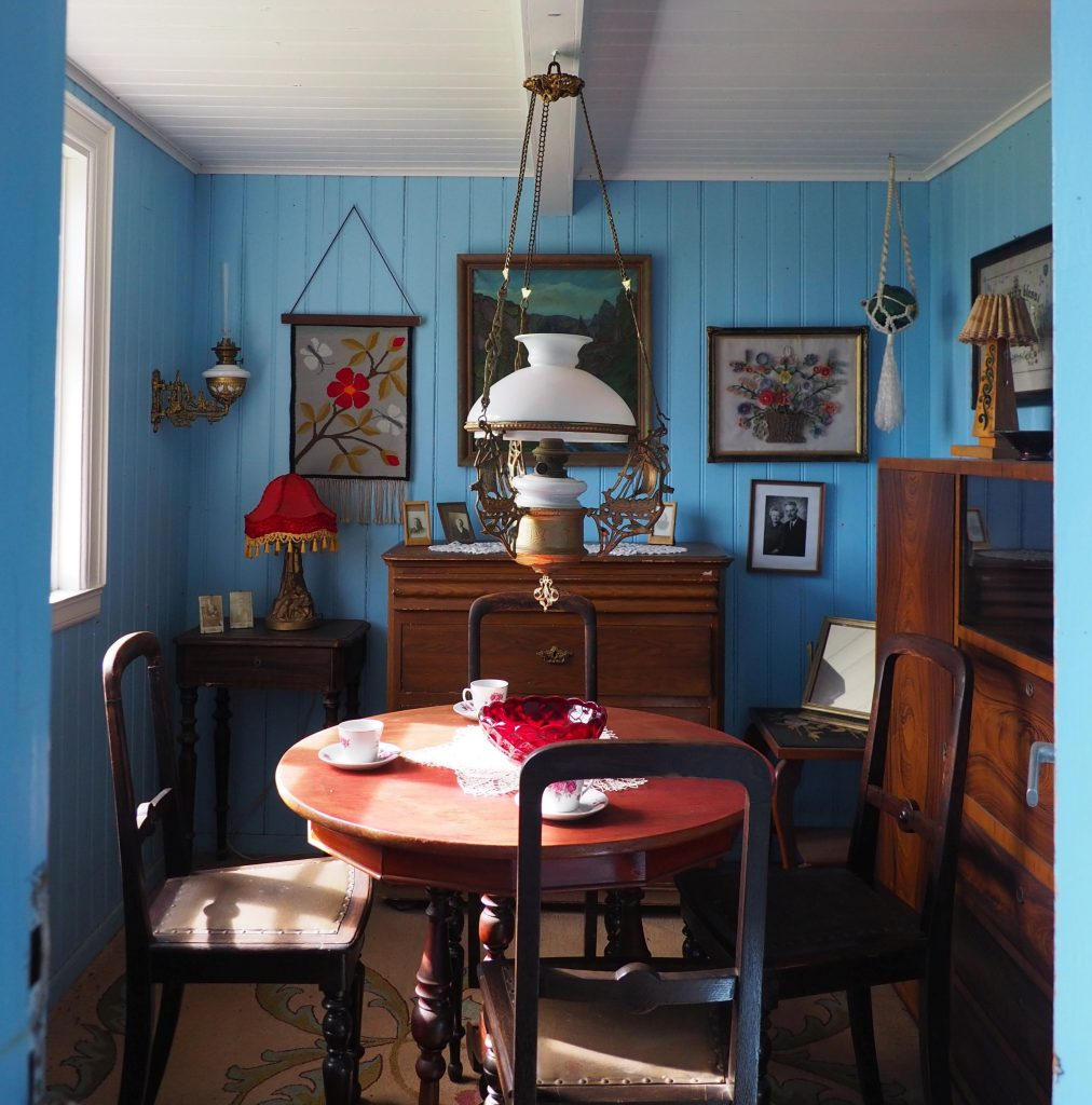 The walls of the small room are blue-painted wood. In the middle is a round wooden table with four chairs around it. A large cupboard is against the right-hand wall: it looks to be a 20th century style, perhaps 20s or 30s. An older chest is agains the far wall, and the left-hand wall has a window. A small table in the corner holds a lamp with a red lampshade. On the far wall a painting hangs above the chest with two more on either side (embroidery, possibly). A white glass lamp hangs above the center of the table, which is set with teacups.