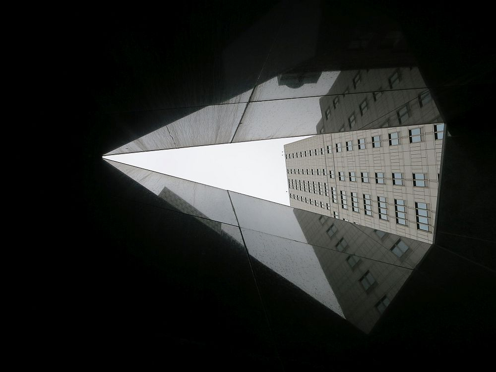 The opening in the ceiling makes a triangular shape, in this view the pointiest part points left. The sky is white and fills about half of the opening, and the federal building fills the other half. The walls are dark and shiny, so they reflect the building and the light of the sky a bit.