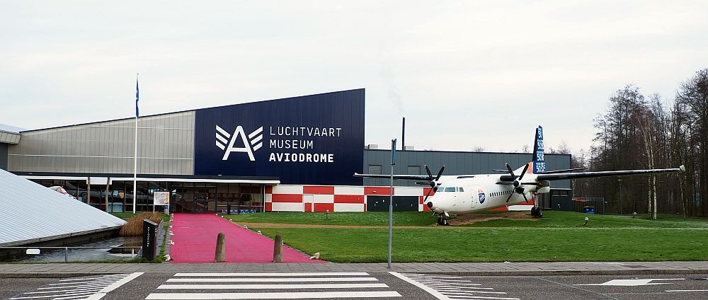 "The building is metal sided, with a roof that slants up from left to right and then has another section visible behind. A large letter A logo with three stripes on either side of it is painted in white on blue above the entrance, next to ""Luchtvaart Museum Aviodrome."" A propeller plane is parked in front of the building."