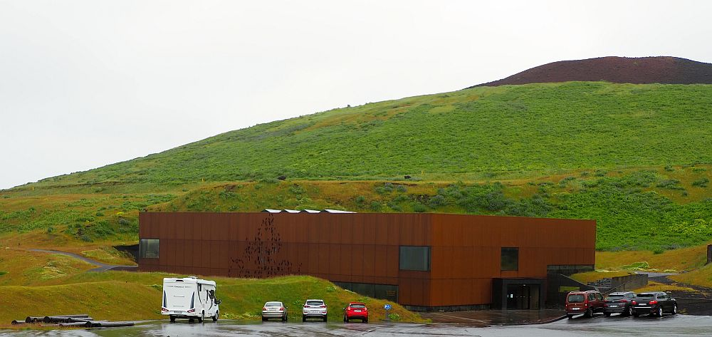 The building is a rust-colored rectangle with only a few windows, set into the ground, more in back than in front. A few cars in a parking lot in front. Behind, the hill is green except at the top, which is black.