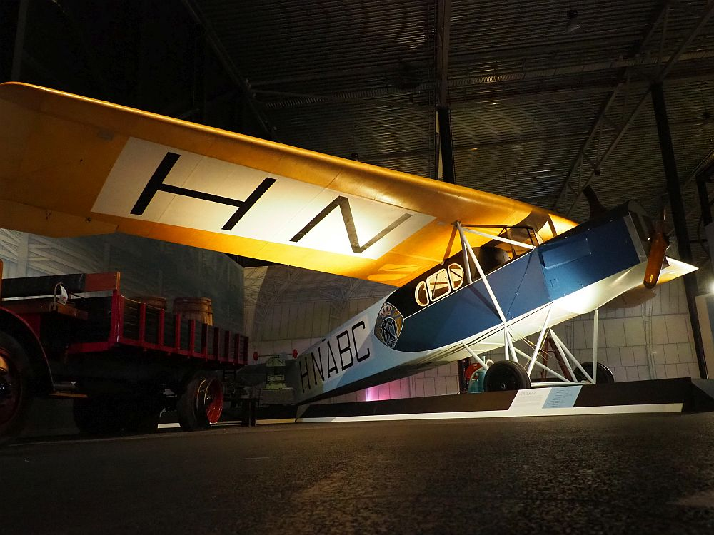 The body of the plane is boxy and mostly blue, with one propeller on the front and the letters HNABC painted on the side. The wing (only one is visible in the photo) is yellow, with the letters HN painted on the underside. Three small windows in the body are where the passengers sat.