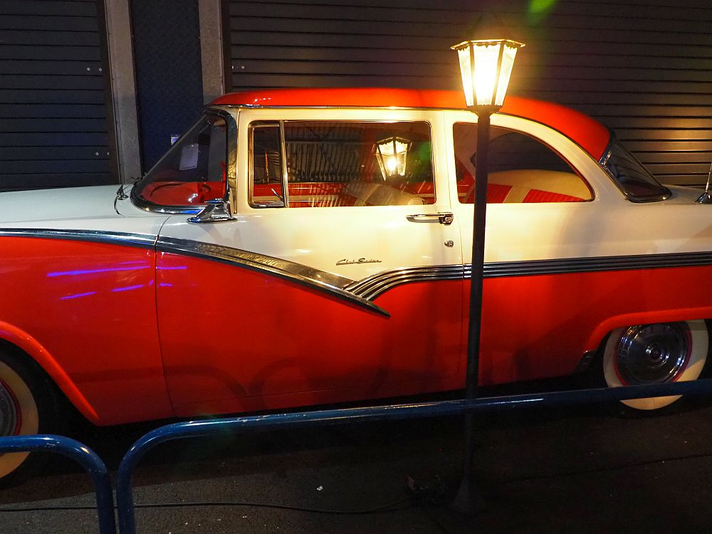 A 50's-style car, painted red and white, with what looks like a street light shining in front of it.