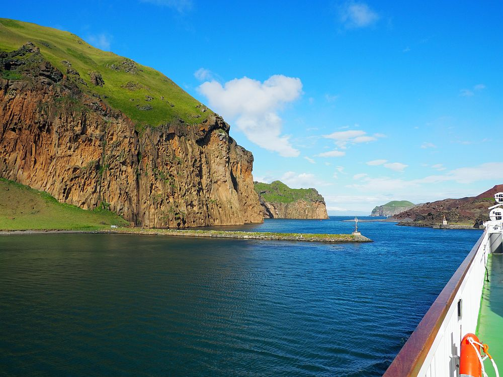 Looking down the side of the ferry, which is along the right side of the photo. Ahead is a view of blue water and the narrow channel the ship passes through. A high brown cliff on the left with a grassy top. More cliffs of the same type further down the channel.