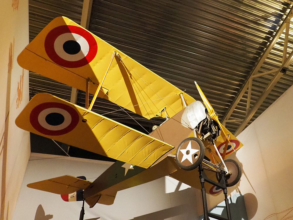 A bi-wing plane, seen from below (It hangs from a corrugated metal ceiling. It has one propeller in front and the wings are painted yellow with a bright round spot at the end of both top and bottom wings: black in the center, then a ring of white, then a ring of red. The body is brown, and the wheels just behind the propeller have white stars painted on them.