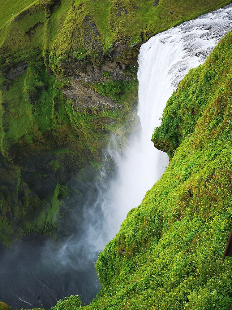 The waterfall plunges down from the top right of the photo toward the bottom left. The water mists outward as well as falling downward. The ground on either side of it is green with low growth.
