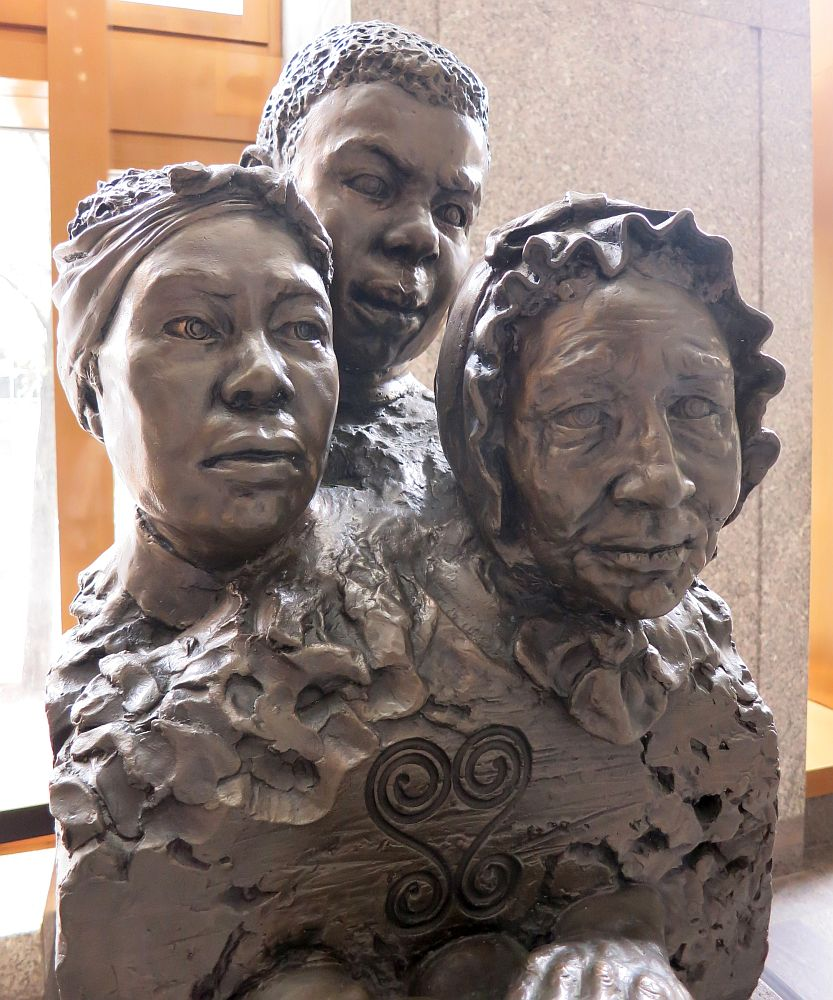 The statue at the African Burial Ground shows 3 people from about the waist up: an old woman in front, wearing a bonnet or hood. Behind her, a younger woman wearing a bandanna. Behind her, a young man with short hair. The statue is made of cast iron or some other metal, I think.
