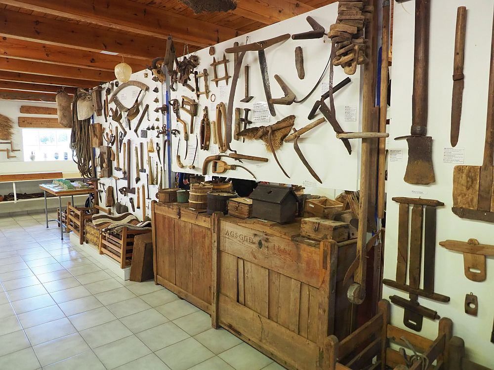A wall has two big chests against it with a range of items on them. On the wall lots of varied implements are hanging: things like scythes and shears and shovels.