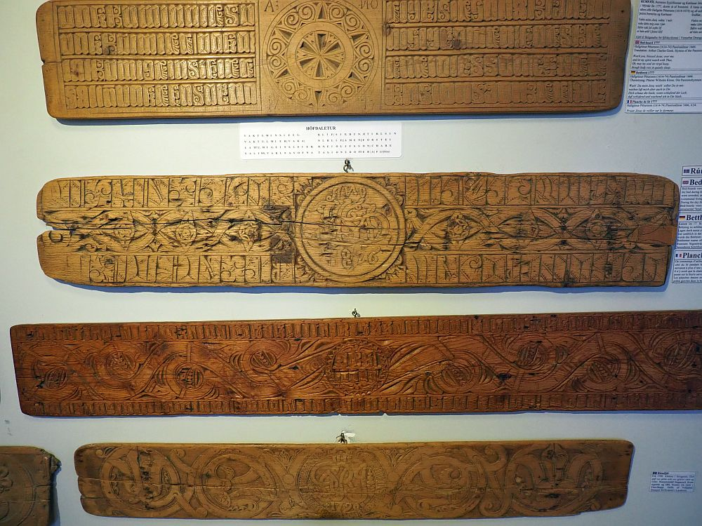 Four bedboards in this photo. Each is more or less rectangualr, but somewhat irregular at the ends. Each has intricate carvings with small primitive images and also lettering.