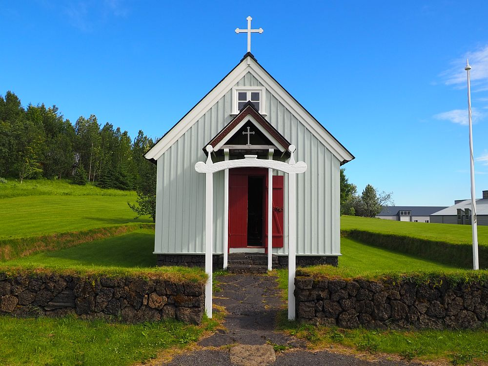 Direct front view of the Skogar Museum's church in Skogar Iceland. It is a wooden building painted white. The roof is peaked and there is a smaller roof over the entrance, also peaked at the same angle as the roof. The front door is red and there is a small cross above it as well as a larger cross on the roof.