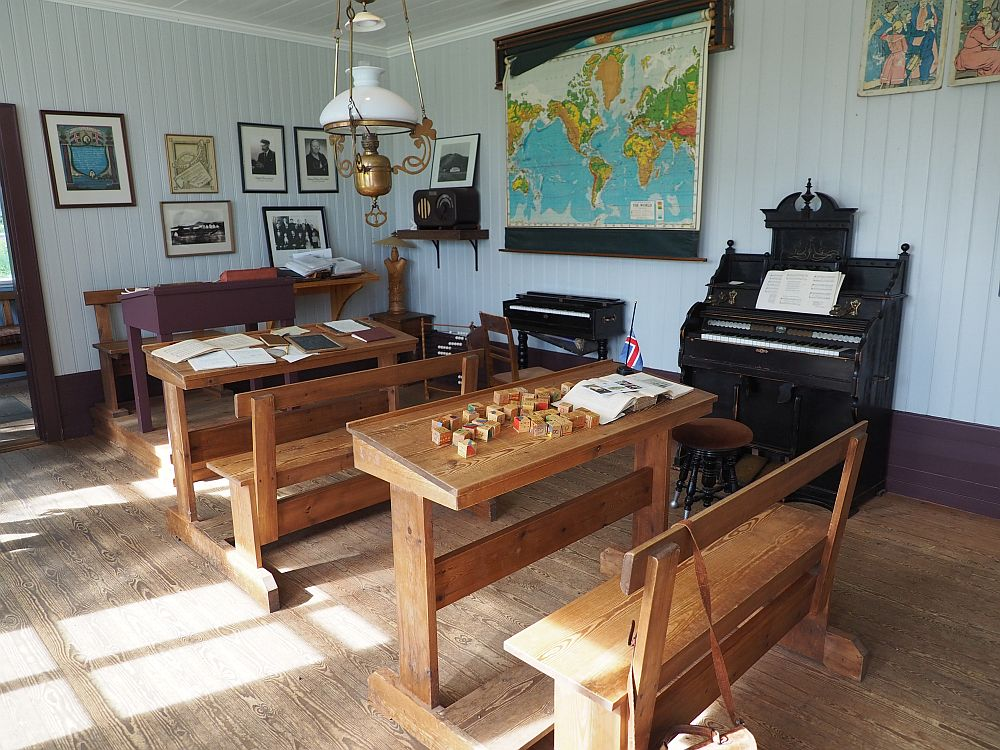 Only two wooden desks with benches fixed to them. Each would sit perhaps three children. The teachers desk is beyond them and set on a small platform. On the wall to the side is a piano and what may be an organ. A world map hangs on the wall.