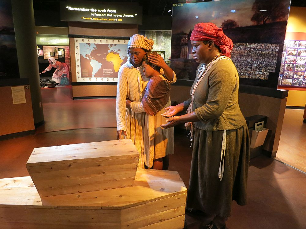 Two women mannequins and a child stand at the end of two plain wood coffins: one full size and one child-sized on top of the larger one. The two women are dressed simply with bandannas on their heads. One holds her hand palm up in front of her, possibly praying. The other woman hugs the child, conforting her. It is a very lifelike image, except that displays of the museum are visible behind them: a map of the slave trade routes behind them.