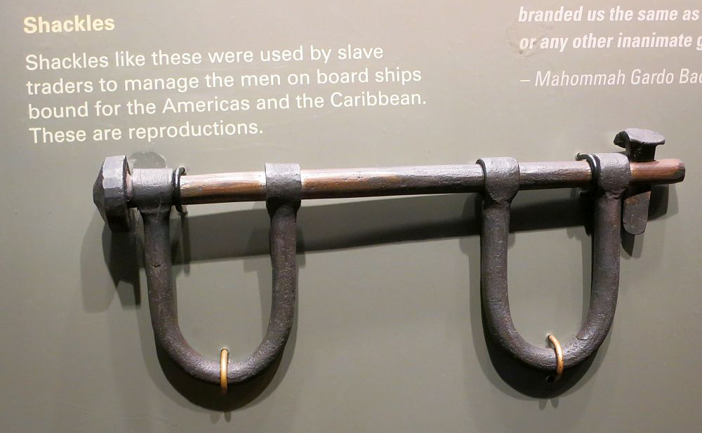 "Shackles: a horizontal iron rod with two U-shaped iron pieces attached to it, where the person's hands would go. The shackles hangs on a wall, printed iwth the caption ""Shackles: Shackles like these were used by slave traders to manage the men on board ships bound for the Americas and the Caribbean. These are reproductions."""