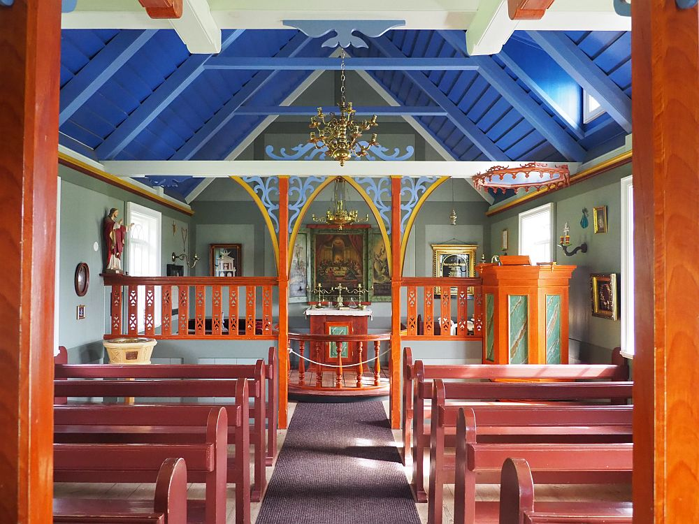 Looking down the aisle, pews on either side, painted reddish pink, only about five rows on either side of the aisle. The altar, straight ahead, has a painting above it and a bronze chandelier above it. Two more paintings are on either side of the altar and a statue of Jesus (?) is on the left-hand wall. The pulpit is before the altar on the right: wood but with a marbled inset on each of 4 or five visible sides. The walls are light green and the ceiling is a bright blue.