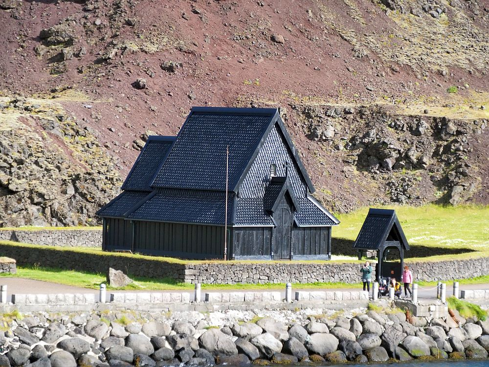 The stave church at Heimaey, Iceland is black and shingled wood. Peaked roof, a smaller peak with a cross over the entrance door. No windows. A low stone wall around it, covered in grass. Bare ground behind it: the edge of the lava field.