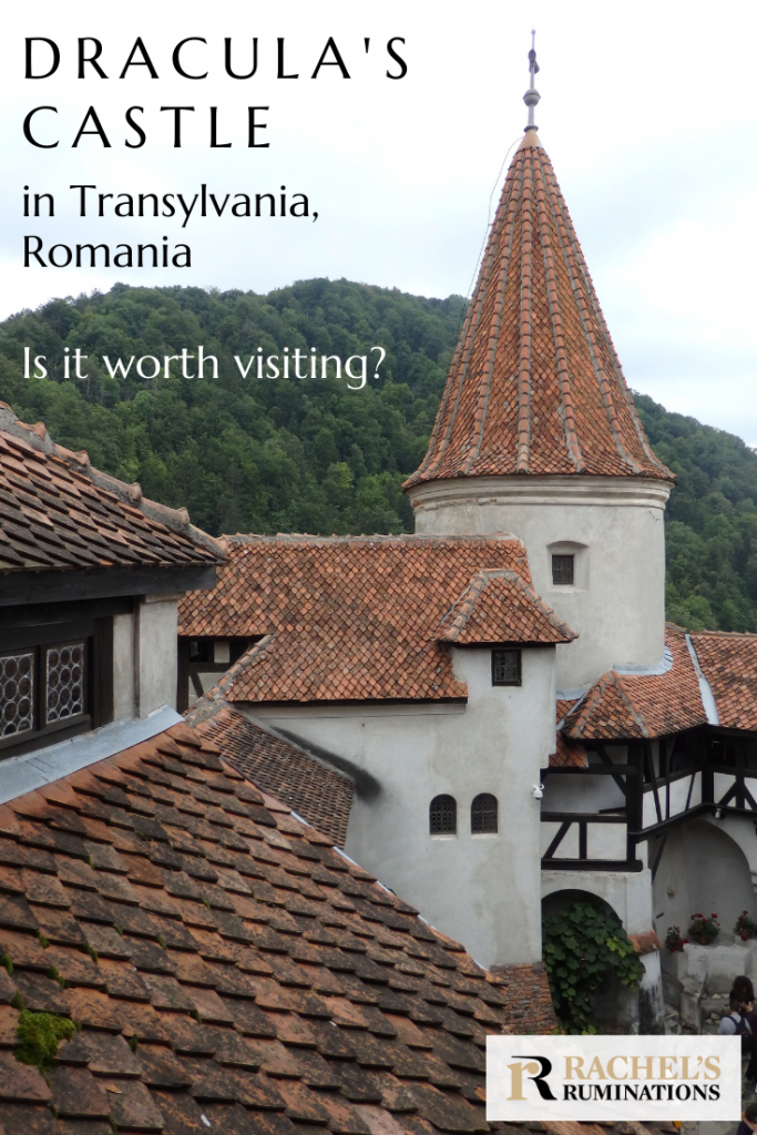 Pinnable image Text: Dracula's Castle in Transylvania, Romania. Is it worth visiting? (and the Rachel's Ruminations logo) Image: looking across roofs of the castle toward a round turret with a red pointy roof. Behind is a tree-covered mountain.