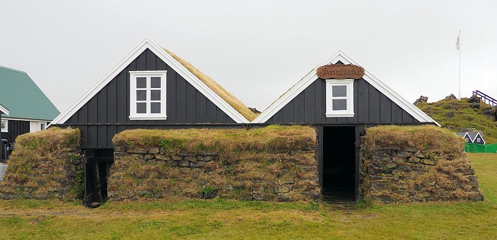 The fisherman's house has two fronts. Only the upper floor of each is fronted with wood. The rest is turf blocks covered in grass. The upper story of each front has a window, edged in white, but otherwise the wood is dark brown.